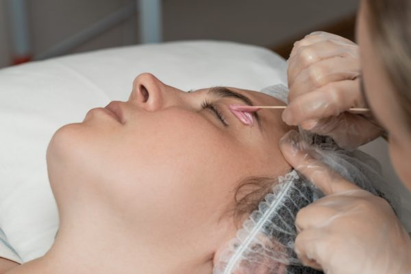 Hand of cosmetologist applying wax paste on armpit