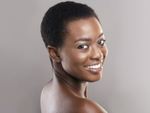 Half-turned beautiful black woman with white smile and clean skin