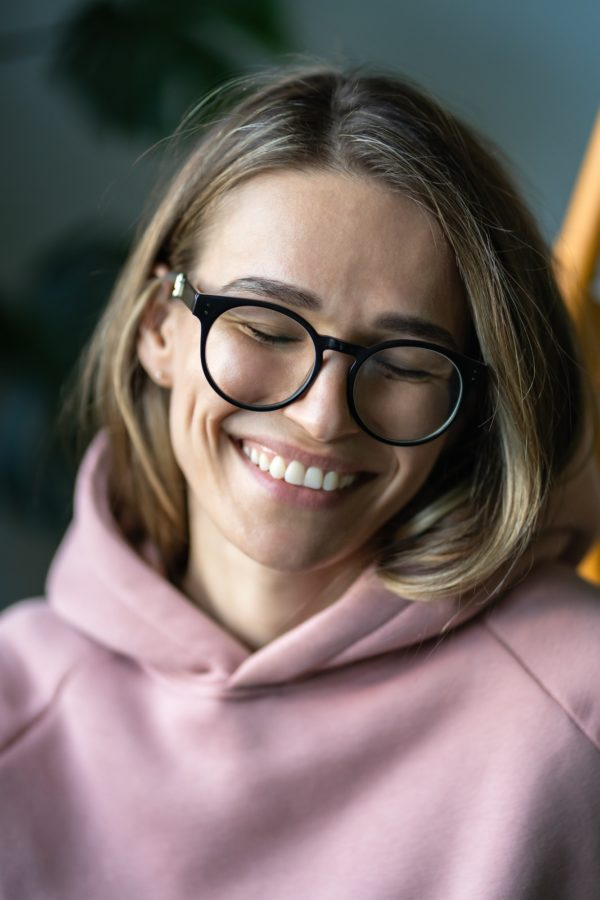 Happy woman with white smile, closed eyes, wearing eyeglasses and pink hoodie. Positive emotion